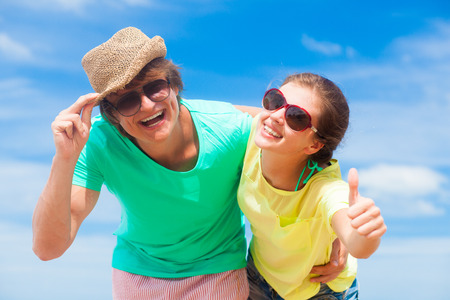 front view of couple having fun at beach  thumbs up photo