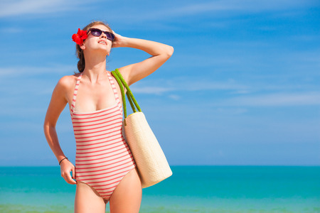 beautiful woman with straw bag at tropical beach photo