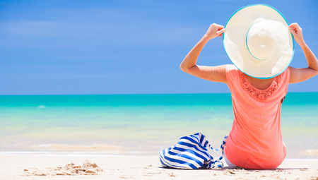 back view of a woman with stripy bag and straw hat sitting on beach photo