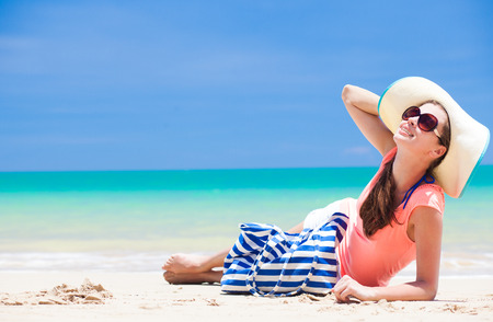 back view of a woman with stripy bag, sunglasses and straw hat sitting on beach photo