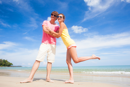 young couple in sunglasses hugging at tropical beach photo