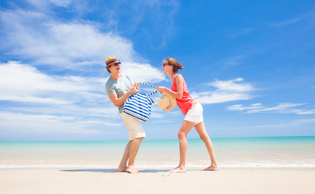 front view of happy young couple running at tropical beach photo