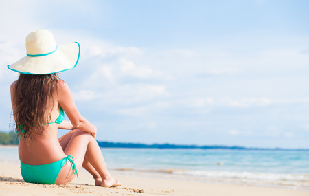 long haired woman in bikini and straw hat bikini on tropical beach Standard-Bild