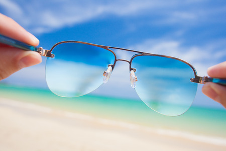 close up of colorful sunglasses. tropical Thailand beach. travel concept photo