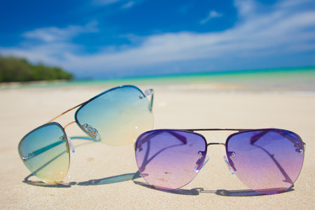 pair of bright sunglasses on tropical Thailand beach. travel concept