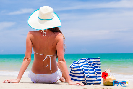 back view of a woman with stripy bag and straw hat at tropical beach photo