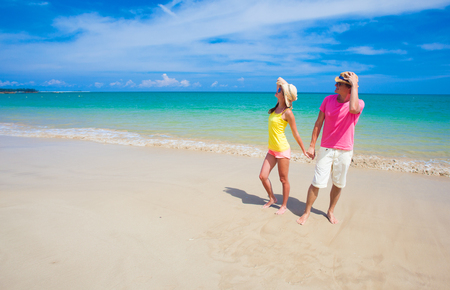 happy young couple holding hands on tropical beach Standard-Bild