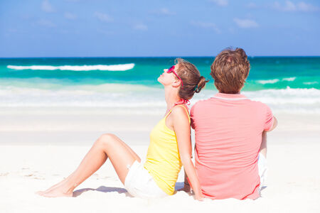 happy young couple sitting at tropical beach photo