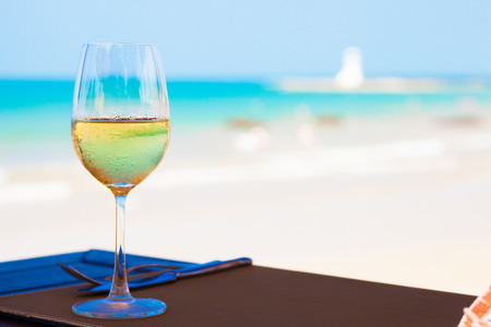 glass of chilled white wine on table near the beach