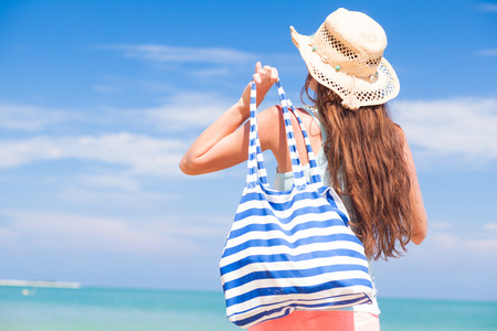 back view of a fit young woman with stripy bag at tropical beach photo