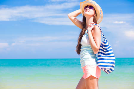 half face view of a fit young woman with stripy bag at tropical beach photo