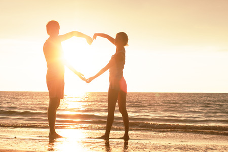 sunset silhouette of young couple in love holding hands in heart shape