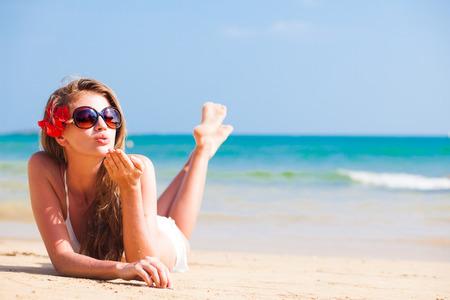 열 대 해변에서 머리에 꽃과 함께 비키니 긴 머리 여자