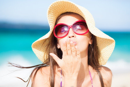 beach kiss: long haired girl in straw hat blowing a kiss on tropical boracay beach Stock Photo
