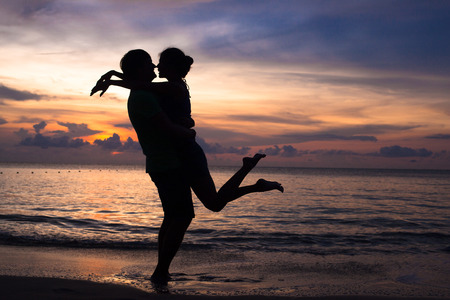 romantik: solnedgång silhuett av unga par i kärlek kramar på stranden