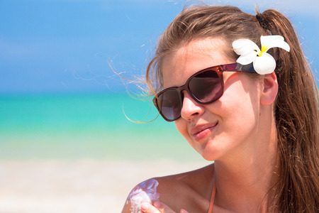 Young woman in sunglasses putting sun cream on shoulder