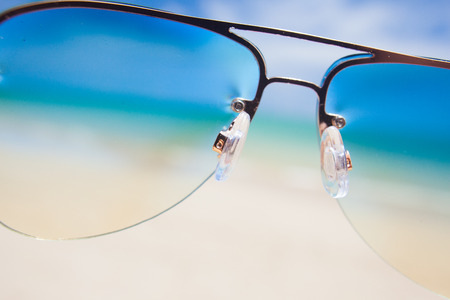 close up of sunglasses. sunny beach in thailand photo