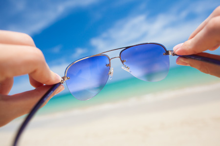 close up of sunglasses. sunny beach in thailand photo