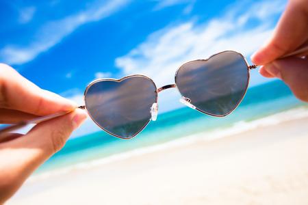 close up of heart-shaped sunglasses. sunny beach in thailand Standard-Bild