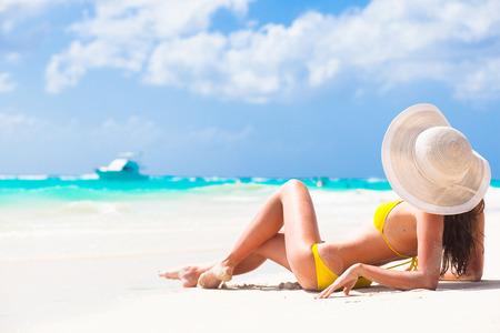 langharige jonge vrouw in bikini en een zonnebril op tropische strand