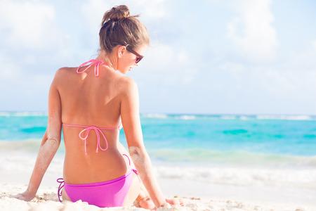back view of long haired woman in bikini on tropical beach Standard-Bild
