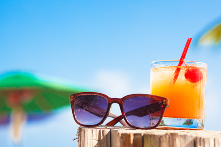 drink at the beach: Rum punch cocktail and sunglasses at tropical beach.