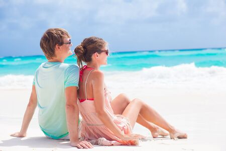 back view of couple sitting on a tropical beach in Barbados photo