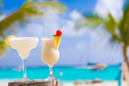 two perfect cocktails pina colada and margarita with cherry on top, beach background photo