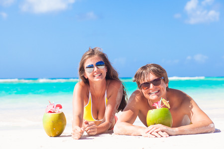 close up of young couple lying on a tropical beach in Barbados and drinking a coconut cocktail