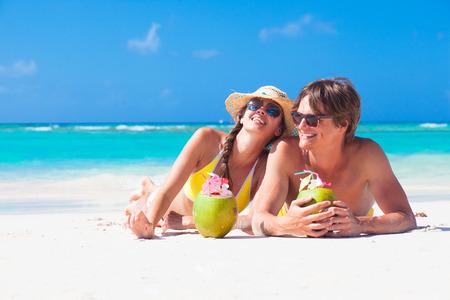 ココナッツのカクテルを飲んで自分の時間を楽しむ若いカップルのクローズ アップ 写真素材