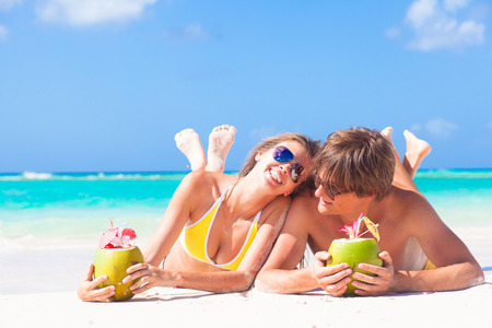 happy young couple lying on a tropical beach in Barbados and drinking a coconut cocktail Standard-Bild