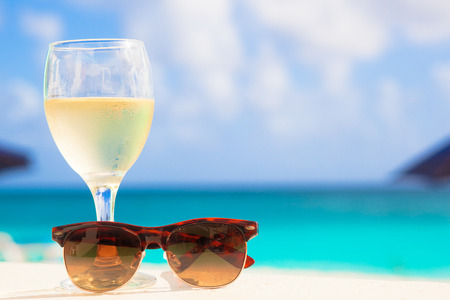 hotel with pool: glass of chilled white wine and sunglasses on table near the beach Stock Photo