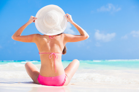 back view of long haired girl in bikini and straw hat on tropical caribbean beach Stock Photo