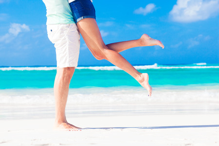 man woman hugging: legs of young kissing couple on tropical turquoise caribbean beach Stock Photo