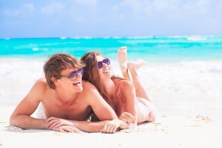 ni�as sonriendo: feliz pareja joven tumbado en una playa tropical en Barbados