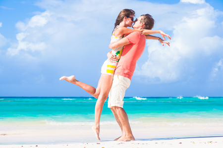 romantic sky: picture of happy couple in sunglasses hugging on the beach