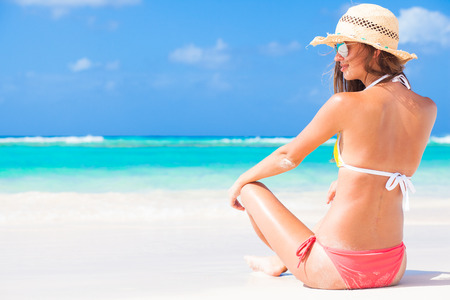 back view of long haired girl in stripy swimsuit and straw hat on tropical caribbean beach