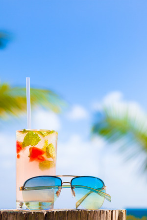 luxury party: glass of chilled cocktail mohito and sunglasses on table near the beach Stock Photo