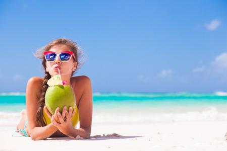 젊은 여자가 해변에서 코코넛과 선글라스에 밀짚 모자에 누워 미소