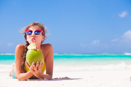 young woman smiling lying in straw hat in sunglasses with coconut on beach