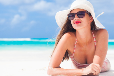 traje de bano: chica de pelo largo en bikini y sombrero de paja en la playa tropical caribe