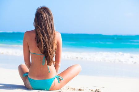 back view of long haired girl in bikini and straw hat on tropical caribbean beach Standard-Bild