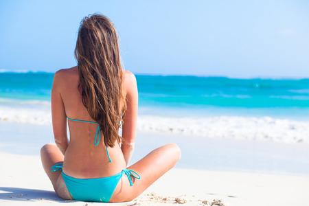 niñas en bikini: Vista posterior de niña de pelo largo en bikini y sombrero de paja en la playa tropical caribe