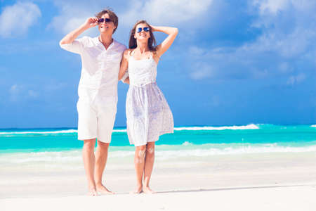 young happy couple in white at tropical beach. honeymoon photo