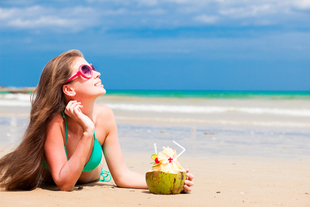 beach drink: Happy young long haired woman in bikini and sunglasses with coconut on the beach
