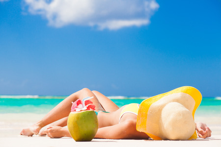 back view of young woman in straw hat with closed eyes on the beach