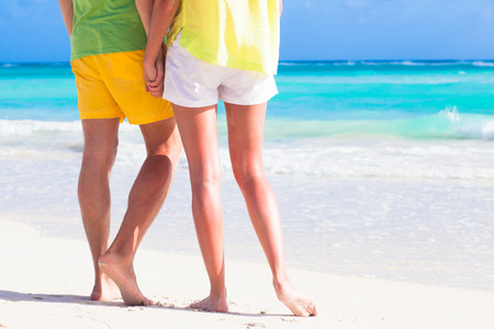 legs of young hugging couple on tropical turquoise beach Standard-Bild