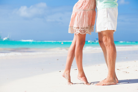 beach feet: legs of young hugging couple on tropical turquoise beach Stock Photo