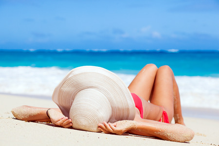 woman in bikini and straw hat lying on tropical beach