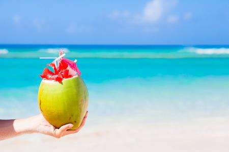 cocotier: cocktail frais de noix de coco avec un parapluie dans la main Banque d'images